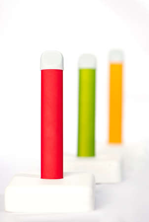 Set of colorful disposable electronic cigarettes on a display stand on a white background. The concept of modern smoking, vaping and nicotine 免版税图像