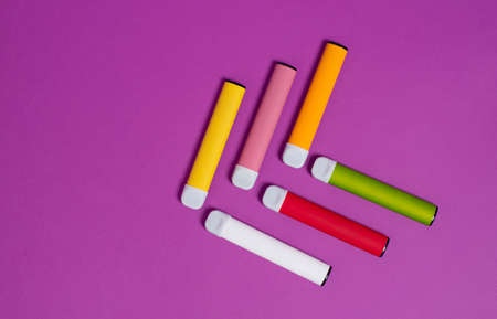 Colorful disposable electronic cigarettes on a purple background. The concept of modern smoking, vaping and nicotine. Top view