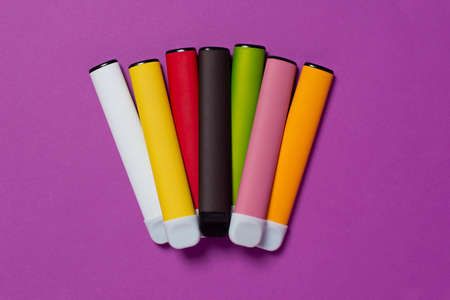 Set of colorful disposable electronic cigarettes on a purple background. The concept of modern smoking, vaping and nicotine. Top view.