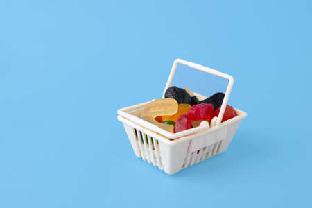 sweet and tasty candy - marmalade, jelly candies, in the toy food basket, shopping trolley on a blue background with space for text