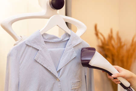 Using steaming iron to ironing shirt in laundry room. Doing stream vapor iron for press clothes in hand. selective focus
