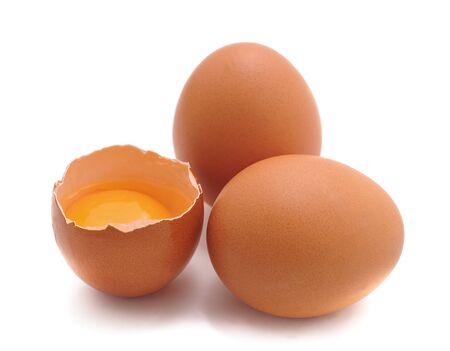 Huevos de gallina y yema de huevo aislado sobre fondo blanco.