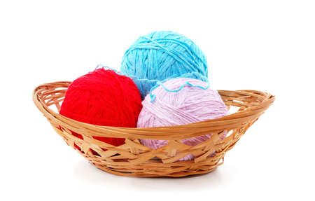 Knitted balls in a basket isolated on a white background.