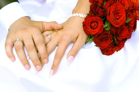 Bride and groom holding hands and a bouquet of red roses photo