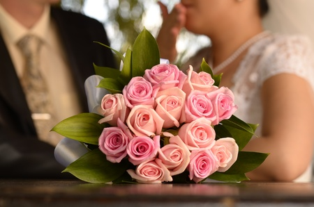 Bouquet of pink roses against a background of the bride