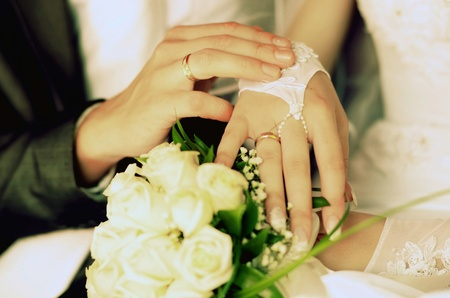 Bride and groom holding hands and a bouquet of red roses