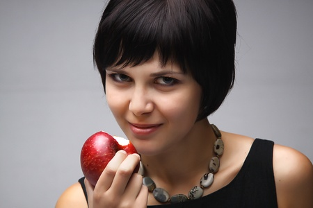Young attractive girl eating ripe red apple Stock Photo