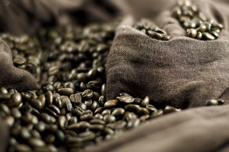 Grains of black roasted coffee on brown cloth Stock Photo
