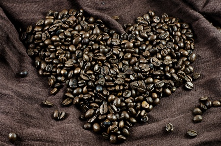 Grains roasted black coffee heart-shaped on brown cloth Stock Photo
