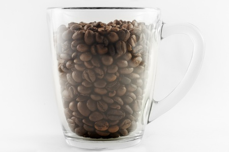 Grains of black roasted coffee in transparent cup isolated on white background
