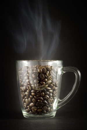 Grains of black roasted coffee in transparent cup with steam on black background Stock Photo