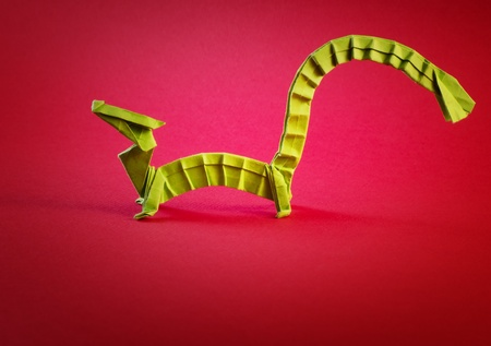 little green dragon origami on red background