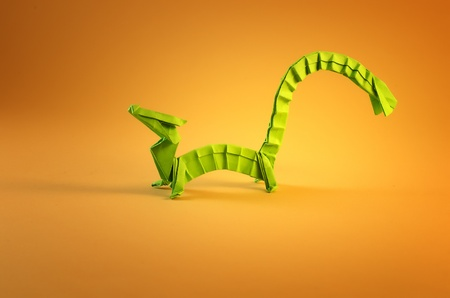 little green dragon origami on yellow background Stock Photo