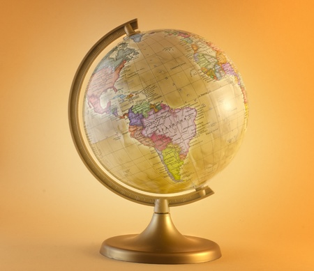 little antique globe isolated on yellow background