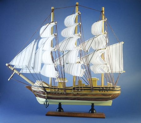 sailing ship toy isolated on blue background photo