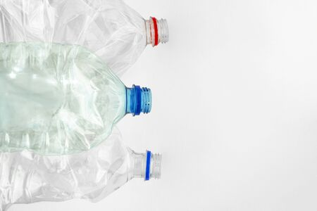 Recycling and separate collection of platik. Crumpled plastic bottles on a white background. Space for text. Plastic pollution of the planet, environmental problems.