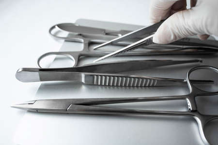 Surgical instruments on a light background. Gloved hand holds a surgical forceps. Medical clamp, scalpel, needle holder