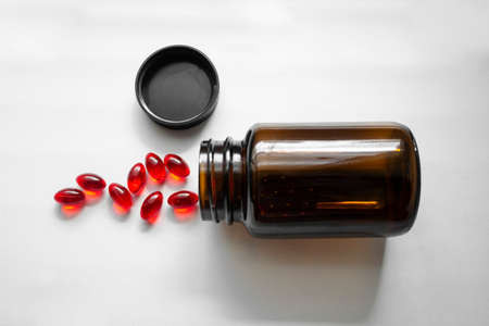 Jars of red pills. Tablets poured out of the jar on white background. Glass brown pill bottle
