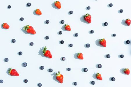 Fruit pattern of blueberries and strawberries. Blue background flatlay