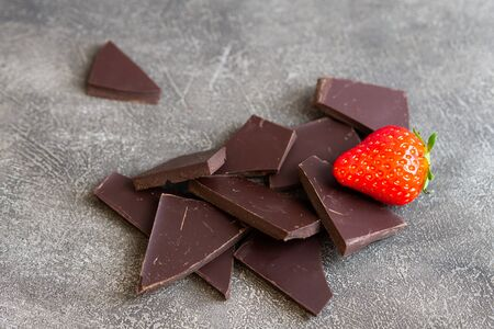 Dark chocolate with strawberry isolated on grey background.
