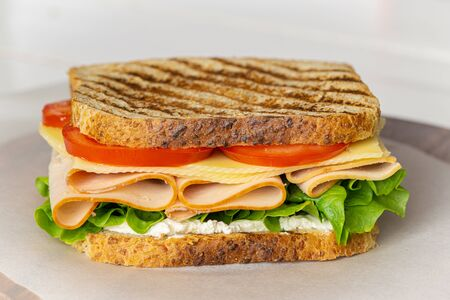 Club sandwich with ham, cheese, lettuce, and tomato. Tasty homemade lunch, breakfast or take away food.