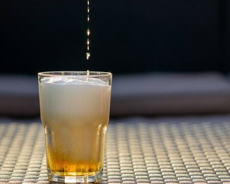 Beer drop falling down to the glass. Freezing motion. Bar, pub, restaurant concept. Copy space, grey background. Banque d'images