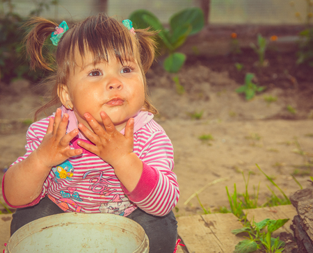 Boa feathers decorate this little girl as she plays princess in a garden. Stock Photo