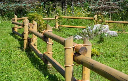 Wooden fence on a green meadow used for horse containment Stock Photo