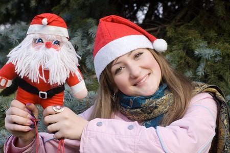 girl smiling holding Santa doll Stock Photo - 3944579