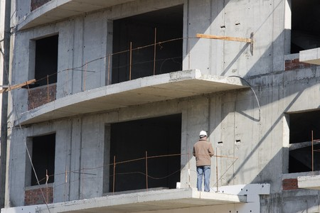 unfinished building: Construction worker facing unfinished building Stock Photo