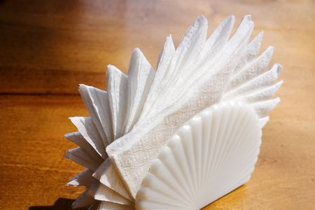 White napkins in sea shell holder against wooden table