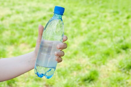 Hand offering bottle of water against green blurred background photo