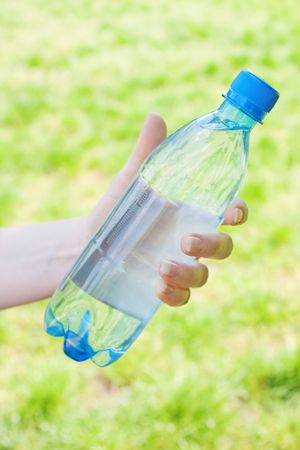 Closeup of hand offering blue bottle of water Stock Photo - 4805850