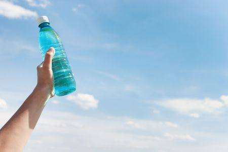 Hand holding bottle of water against blue sky with white clouds photo