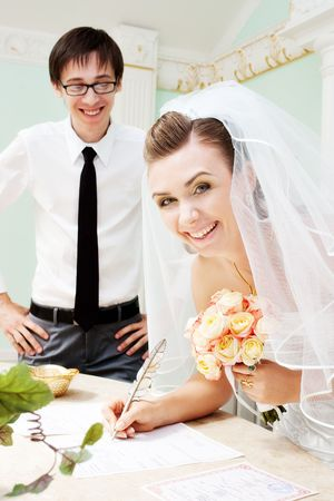 Bride signing marriage certificate and laughing with blurred groom