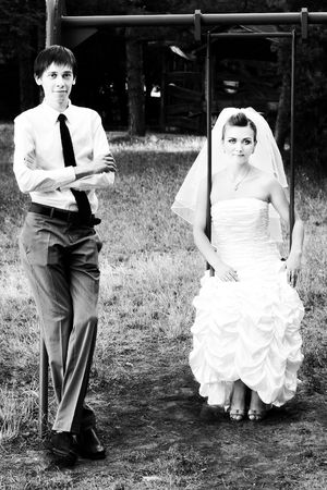 Black and white photo of bride sitting on swings and groom standing near   photo
