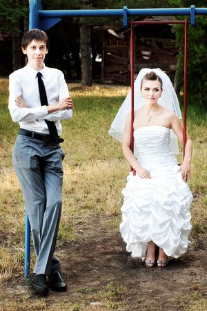 Bride sitting on swings and groom standing near  photo