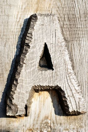 Capital letter A carved from wood with wooden texture in the background photo