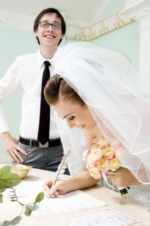 Smiling bride signing marriage certificate and blurred groom in glasses laughing   photo