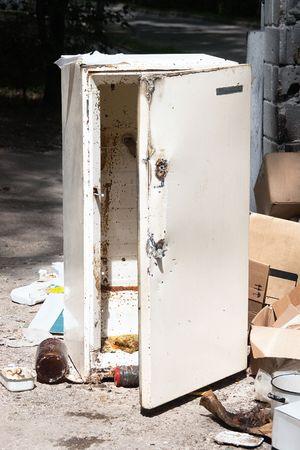 Old broken fridge on junk yard with decaying food inside