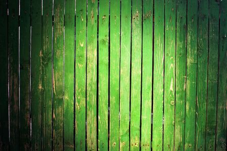 picket green: Grungy green picket fence with peeling paint and light spot Stock Photo