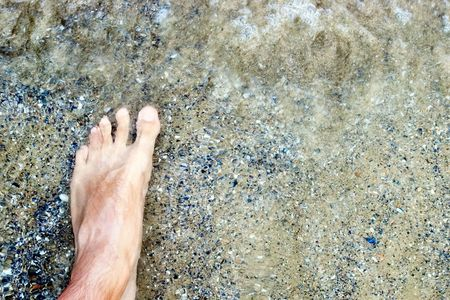 Male foot in swirling sea water stepping on the shell rock sand photo