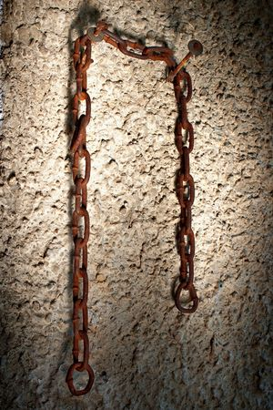 Rusty old chain hanging on two nails in lime wall with dark edges   photo