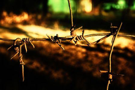 Rusty barbwire against blurred fiery dark background photo