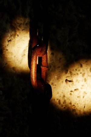 Rusty old chain link against lime wall with two lightspots photo