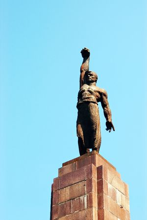 Bronze statue of soviet working man with clenched fist against sky in Chisinau city photo