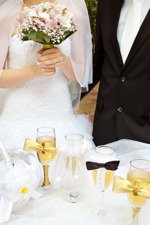 Part of bride and groom near wedding decorated table with wine glasses, selective focus on bouquet photo