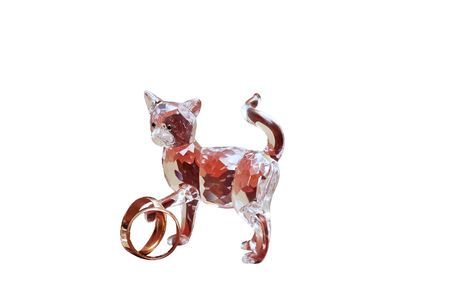 cutglass: Cut-glass crystal cat with two wedding rings isolated on white