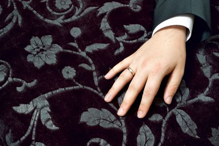 Closeup of groom's hand with wedding ring on black velvet with floral pattern Stock Photo - 5522648