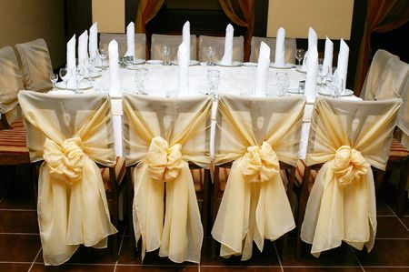 Table set for wedding reception with golden cloth bows on decorated chairs